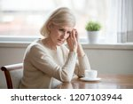 worried senior woman sitting at ... | Shutterstock . vector #1207103944