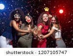 Stock photo fun at new year party happy women celebrating and posing with photo props and champagne 1207105747