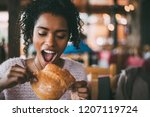 black woman eating bread | Shutterstock . vector #1207119724