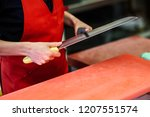 young female butcher sharpening ... | Shutterstock . vector #1207551574