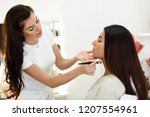 makeup artist making up an... | Shutterstock . vector #1207554961