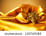 Golden glamour theme with sparkling christmas star over light brown background. Studio shot - stock photo