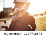 a handsome biker fastens his... | Shutterstock . vector #1207718641