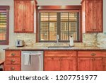 Stock photo wooden kitchen room with stone backsplash granite countertops and stainless steel appliances 1207751977