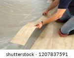 work on laying flooring. worker ... | Shutterstock . vector #1207837591