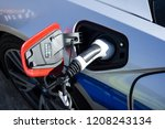 electric vehicle is plugged... | Shutterstock . vector #1208243134