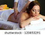 beautiful young woman in spa salon getting massage, isolated on white - stock photo
