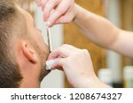 shave a man's beard with a... | Shutterstock . vector #1208674327