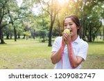 sport woman holding green apple ... | Shutterstock . vector #1209082747