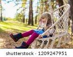 cute girl swinging in a hanging ... | Shutterstock . vector #1209247951