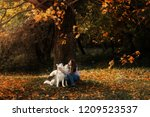 Stock photo girl plays with her husky dog in fallen autumn leaves 1209523537