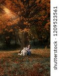 Stock photo girl plays with her husky dog in fallen autumn leaves 1209523561