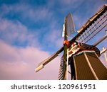 Dutch Windmill on the Waterfront of a Lake with Spectacular Clouds - stock photo