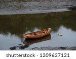 A wooden rowboat is left...