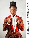 Small photo of Portrait of a confident African business woman wearing an African print suit with a sophisticated hair holding her bow tie