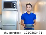 young man holding stack of... | Shutterstock . vector #1210363471