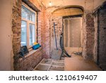 Interior of small room with window and bricks walls in an apartment that  is under construction, remodeling, renovation, extension, overhaul  and reconstruction. - stock photo