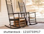 Two wooden pretty rocking chairs on front porch of a farm house.