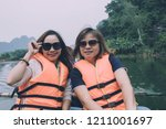 two asian woman tourist wearing ... | Shutterstock . vector #1211001697