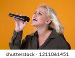 beautiful blonde girl singing... | Shutterstock . vector #1211061451