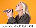 beautiful blonde girl singing... | Shutterstock . vector #1211061454
