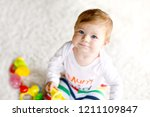 adorable baby girl playing with ...   Shutterstock . vector #1211109847