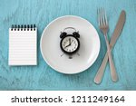 clock on white plate with fork  ... | Shutterstock . vector #1211249164