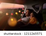 young couple sitting in their... | Shutterstock . vector #1211265571
