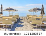 beach umbrellas and couches on... | Shutterstock . vector #1211283517