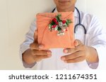 doctor holds a gift box ... | Shutterstock . vector #1211674351