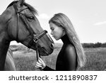 girl rider stands next to the... | Shutterstock . vector #1211890837