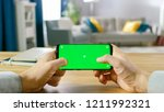 Small photo of First Person Close-up of the Man Holding Green Screen Smartphone in Landscape Mode and Playing Game with His Thumbs.
