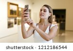 attentive girl taking photo by... | Shutterstock . vector #1212186544