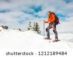 Small photo of Winter climbing the mountain. A man in snowshoes is climbing to the top. Winter ascent. A mountaineer with a backpack and trekking sticks. Equipment for winter hiking.