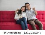 sweetheart couple watching tv... | Shutterstock . vector #1212236347