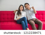 sweetheart couple on red sofa... | Shutterstock . vector #1212238471