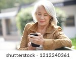 beautiful senior woman texting ... | Shutterstock . vector #1212240361