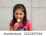 Small photo of Little girl laughing while eating chocolate ice cream. Smiling young kid portrait on pink t shirt with full mouth eating cold dessert. Dirty, mess, fun, childhood joy concepts