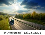 Small photo of Green truck driving on the asphalt highway between deciduous forest in autumn colors under the radiant sun and dramatic clouds. View from above.