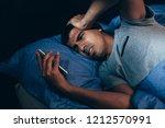 sleeping man being woken up by... | Shutterstock . vector #1212570991
