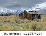 Small photo of Lonely wooden cabin decaying in the rugged wilderness under the snowy mountains in California. Picturesque view of an abandoned hut destroyed by the elements in the ruthless American wilderness.