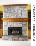 Natural Gas fireplace built with stone and wooden mantels in family room of modern home - stock photo