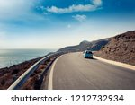 blue small car rides along a...   Shutterstock . vector #1212732934