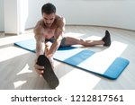 muscular man stretches at the...   Shutterstock . vector #1212817561