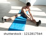 muscular man stretches at the...   Shutterstock . vector #1212817564
