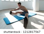muscular man stretches at the...   Shutterstock . vector #1212817567