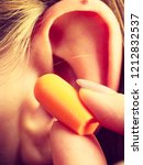 woman putting ear plugs into... | Shutterstock . vector #1212832537