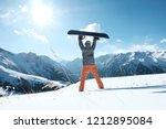 snowboarder raises a snowboard... | Shutterstock . vector #1212895084
