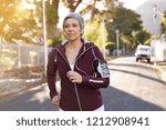 senior woman jogging on street... | Shutterstock . vector #1212908941