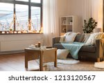 Small photo of interior, christmas and interior concept - cushioned sofa, coffee table, garland string and candles on window sill in living room of cozy home